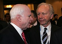 John McCain talking with Joe Lieberman in a narrow, busy hallway at a conference
