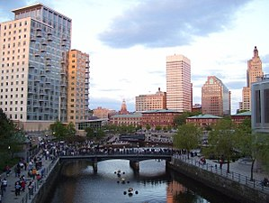 Providence, Rhode Island - People gathering in Waterplace Park, opened in 1994, just before a WaterFire event. On the left can be seen the Waterplace condominiums, constructed in 2008. The entire area had been covered in railroad tracks, and the river was covered with paved bridges until the late 1980s.