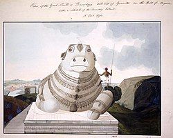 A huge bull, with large eyes, carved out of stone and ornamented with many necklaces, is seated on a stone altar built atop a hill and overlooking the plains behind. The bull's left front paw is extended out; its right, folded under. An adult man, shown in the picture, is dwarfed by comparison.