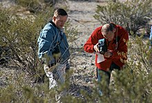Aldrin, wearing a red peacoat, holding a large camera with his left hand and balancing it with his right. The camera is pointed at the ground. Armstrong wears a blue jacket and khakis, and looks near where Aldrin points the camera. There is a desert background, with sparse desert bushes.