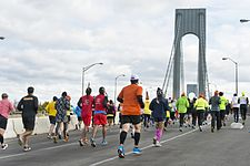 Três corredores em uma corrida por uma rua onde os espectadores estão torcendo atrás das barreiras.