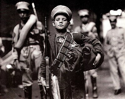 Boy soldier during the Mexican Revolution, Archivo Casasola. Huerta massively expanded the army by forced recruitment to fight the revolutionaries opposed to his regime. Boy soldiers in the Federal Army were not unusual. Nino Soldado.jpg