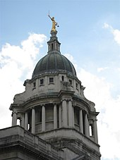 The stone dome at the top of a building, columns below, with a bronze statue on top depicting a woman holding a sword in one hand and a pair of scales in the other