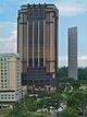 Distant view of a 25-storey building with a bronze facade and several vertical ridges that continue upward to the roofline