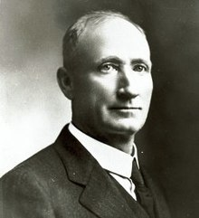 Clean shaven man with receding hairline in a coat and tie