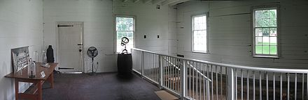 White pained interior of a room with wooden walls, three windows, and door. There is a wooden table at left and a white railing at left.
