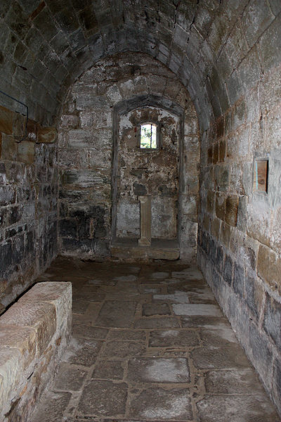 English:  The passage of the deads, between the Church and the chapter house. The condemned door leads to the cemetery. The bunk was used for ablution of the dead before burial in the cemetery nearby.