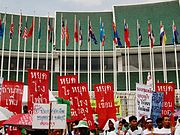 Many people holding signs in front of a building with green layered roofs; many national flags on flag poles lined in two rows in front of the building