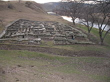 Large, low stone construction (with people walking past for scale) near a river