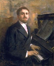oil painting of a white man, sitting at a piano but looking towards the viewer. The man has neat brown hair, a moustache and neat beard.