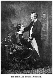 A couple is shown. On the left is a tall woman of about 30, she wears a voluminous dress and is sitting sideways in an upright chair, facing and looking up into the eyes of the man who is on the right. He is about 60, quite short, balding at the temples, he is dressed in a suit with tailcoat and wears a cravat. He faces and looks down at the woman, his hand rests on the back of the chair.