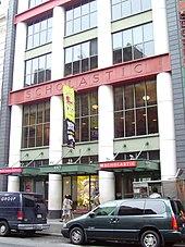 Façade vitrée d'un immeuble comportant quatre colonnes blanches. Au 2/3 de hauteur de la photo est visible le nom de l'éditeur «Scholastic» sur fond rouge.