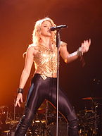 A lady is singing a song dressed in a mesh gold crop top coupled with skin-tight leather pants. She is singing in front of a mic stand.