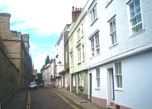 A narrow road, pavements either side; on the left, a stone wall; on the right, a row of terraced three-storey houses, the upper storeys overhanging the ground floor