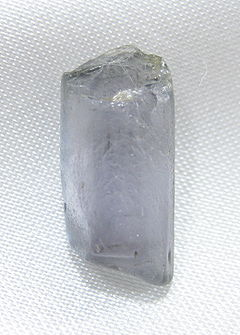 A long crystal of light purple sillimanite on a white background.