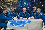 Soyuz MS-08 crew and backup crew sign a flag in the museum.jpg