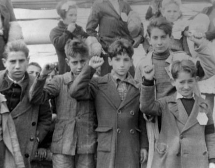 Children preparing for evacuation, some giving the Republican salute. The Republicans showed a raised fist whereas the Nationalists gave the Roman salute. Spanish War Children (restored).png