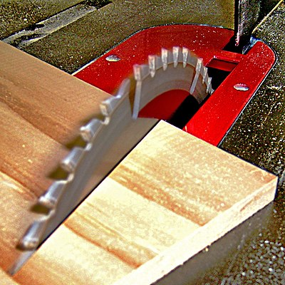 The blade of a table saw cutting into wood Table saw cutting wood at an angle, by BarelyFitz.jpg
