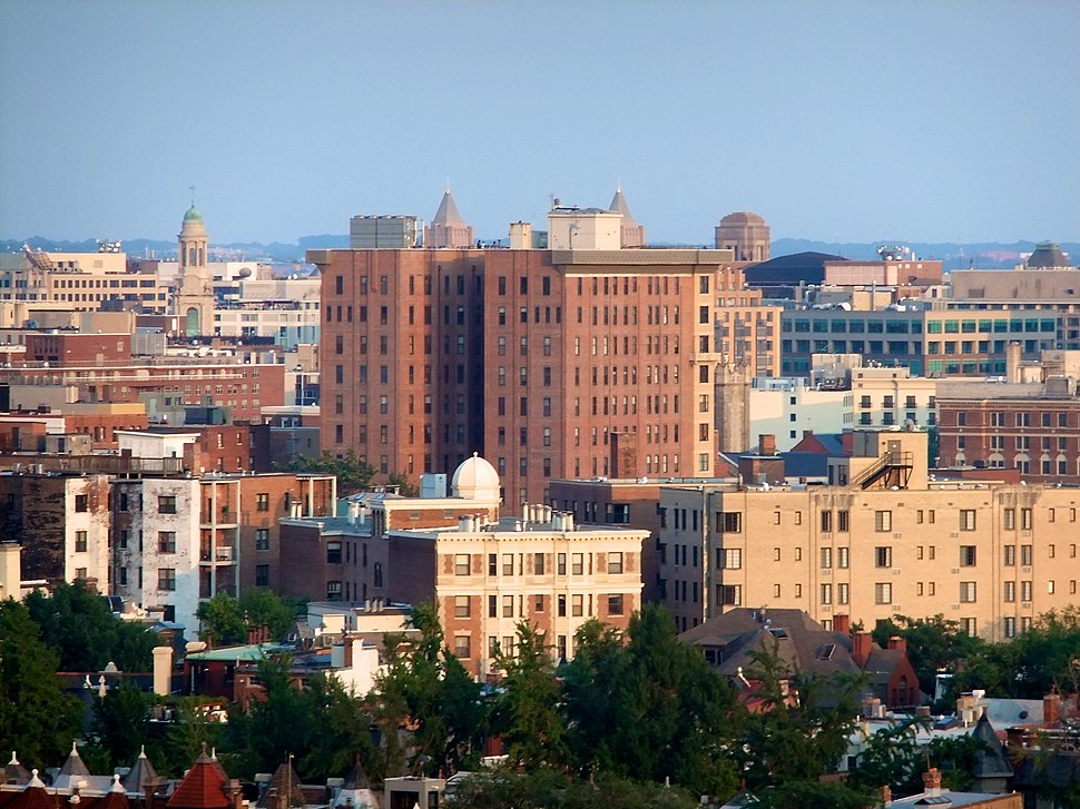 A tall red brick building in the center of a city skyline punctuated by steeples and other shorter buildings.