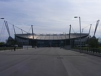 A straight tarmac road. At the head of the road is a stadium with a bowl-shaped outline, surrounded by a number of masts, with cables running to the stadium roof