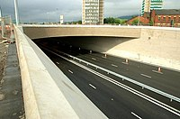 Empty motorway underpass with three lanes either side of the central barrier.