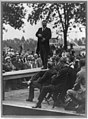 Theodore Roosevelt standing on table outdoors and making speech to men seated around him, hands at waist) - Smith Art Photography, Freeport, Ill LCCN91787239.jpg