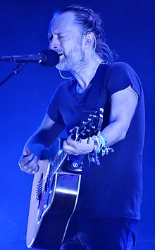 Yorke playing an acoustic guitar and singing into a microphone