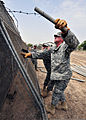 U.S. Army Spc. Steven Klinger, right, with 2nd Battalion, 137th Infantry Regiment, Kansas National Guard, untangles barbed wire from a gate at the canine training course at the police academy in Djibouti Sept 100901-N-AT895-022.jpg