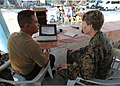 U.S. Marine Corps Capt. Amelia Griffith, right, a civil affairs officer with the Joint Civil Military Operations Task Force, reviews a presentation with Philippine Marine Corps Capt. Mike Mortel during a social 130318-N-VN372-009.jpg