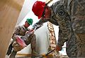 U.S. Marine Corps Lance Cpl. John M. Toniolo, left, a combat engineer with the 9th Engineer Support Battalion, 3rd Marine Logistics Group, holds a baseboard steady as Army Staff Sgt. Matthew Zawel, a site 130722-M-MG222-006.jpg