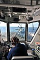 U.S. Navy Ensign Heather L. Wilkins communicates with the pilots of an MH-60R Seahawk helicopter attached to Helicopter Maritime Strike Squadron (HSM) 70 from the helicopter control tower aboard guided missile 111017-N-YZ751-077.jpg