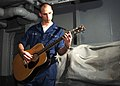 US Navy 021201-N-6817C-001 Sailor enjoys playing his guitar during some leisure time aboard the aircraft carrier USS Abraham Lincoln (CVN 72).jpg