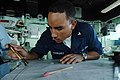 US Navy 060216-N-4374S-011 Quartermaster 3rd Class Carlos Rodriguez, assigned to the amphibious dock landing ship USS Carter Hall (LSD 50), plots the ship's current position on a chart.jpg