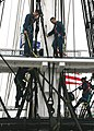 US Navy 060829-N-5322S-004 USS Constitution's mizzen mast crew stands on the fighting top as safety observers, while chief petty officer selectees climb the shrouds during up-and-over exercises in the second week of CPO leaders.jpg