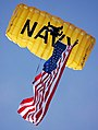 US Navy 070308-N-4163T-356 A member of the U.S. Navy Parachute Demonstration Team Leap Frogs descends into San Diego's Qualcomm Stadium with the American flag during a training session.jpg