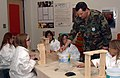 US Navy 070427-N-2143T-005 Chief Construction Electrician Mark Thresher assigned to Naval Facilities Engineering Command teaches kids at East Port Orchard Elementary school how to properly use a paint brush.jpg