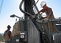 US Navy 070814-N-1205P-046 Construction Mechanic 2nd Class Matthew Vajgrt, an instructor assigned to the 31st Seabee Readiness Group, disconnects a water pump line from the drill rig.jpg