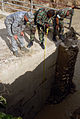 US Navy 080918-N-3595W-385 Air Force engineers and Navy Seabees embarked aboard the amphibious assault ship USS Kearsarge (LHD 3) inspect a bridge in a small community between Cabaret and Cazales that was damaged by Hurricane I.jpg