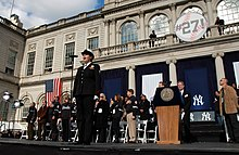 "A woman in an American Navy uniform stands before a microphone with several people behind her on stage. The stage is in front of a building with a sign that reads ""#27!""."