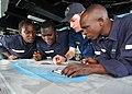 US Navy 100412-N-6138K-381 Ensign Michael Manaskie shows APS students how to use a nautical navigation chart aboard the amphibious dock landing ship USS Gunston Hall (LSD 44).jpg
