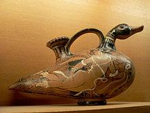 Vase en forme de canard décoré de femmes nues volant au milieu de plumages stylisés.