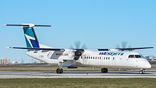 WestJet Encore Q400 aircraft with propellers taxing at an airport
