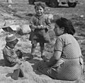 Woman and children playing in the sand at the Community Housing Project. - NARA - 285773 (cropped).jpg
