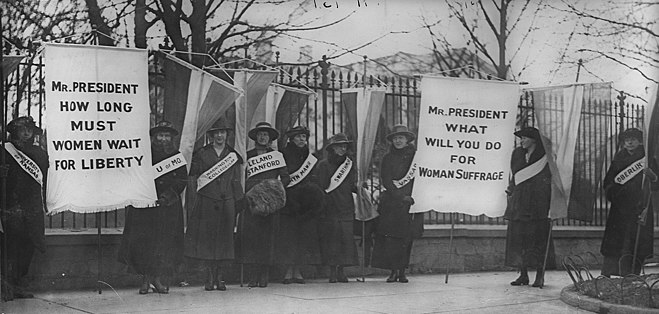 "The Silent Sentinels, women suffragists picketing in front of the White House circa February 1917. Banner on the left reads, ""Mr President, How long must women wait for Liberty?"", and the banner to the right, ""Mr President, What will you do for women's suffrage?"" Women suffragists picketing in front of the White house.jpg"