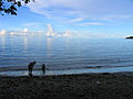 Young girl and a child (silhouetted) play on the beach at Kakambona, west of Honiara. (10660468075).jpg
