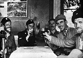 a black and white photograph of uniformed males seated around a table, several are holding glasses