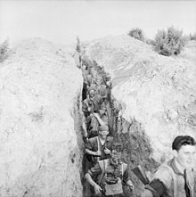 A deep trench line runs vertically from the top to the bottom of the photography, while on either side is a bare earth bund. Nine Caucasian soldiers carrying weapons, ammunition, and other equipment, many with their faces blacked and wearing camouflage on their heads, move in a straight line down the trench towards the bottom of the photo, below the camera. At the bottom right of the photo, a soldier stands level with the camera facing the right at the head of the patrol.