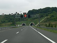 Variable traffic signs placed on a gantry spanning three motorway lanes. The sign informs of overtaking ban for freight vehicles being enforced and that current temperature is 17 degrees Celsius. A two-tube tunnel portal is visible in the background.