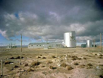 SL-1 - The ALPR before the accident. The large cylindrical building holds the nuclear reactor embedded in gravel at the bottom, the main operating area or operating floor in the middle, and the condenser fan room near the top. Miscellaneous support and administration buildings surround it.
