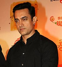 An Indian man wearing a black dress shirt.